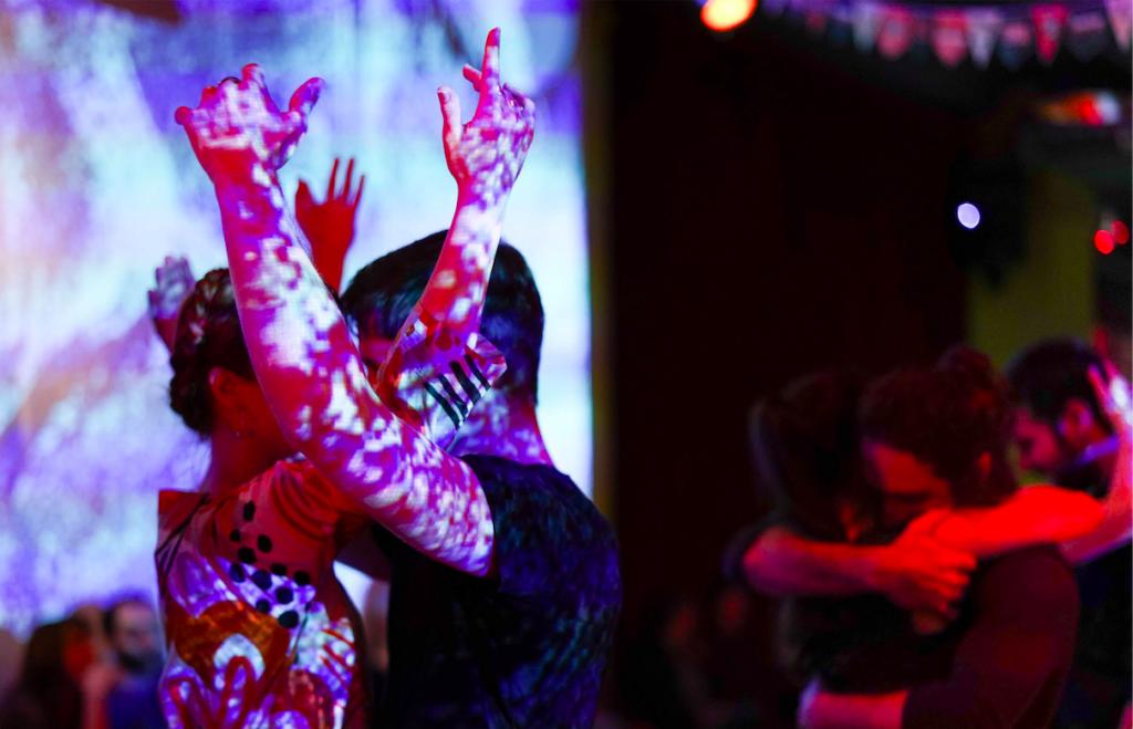 Die Berliner lieben den Tango: Ein Tanzpaar bei der Domilonga vor einer Wand mit einer Videoprojektion.